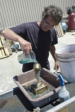 Baxter pours a secret chemical mix over the sculpture to create the patina. - PHOTO BY STEVE E. MILLER
