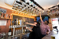 """DRINK LIKE A LOCAL:  Baywood Ale House Manager Christopher Mayes (left) and Owner Chad Carroll reach for their coveted """"local"""" mugs, of which there are 100. Currently, 300 people are waiting to get on the loyalty program list. - PHOTO BY KAORI FUNAHASHI"""