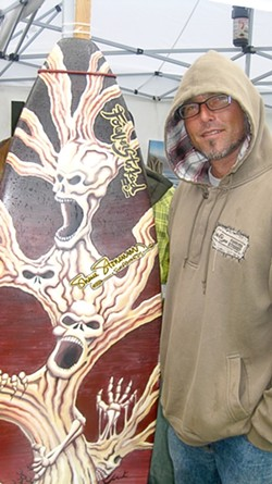 HAUNTED SURFBOARD :  Thanks to the weather, Chris Pedersen of Forever Stoked sold a number of hats at the Nas and Damian Marley concert. - PHOTO BY NICK POWELL