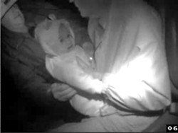 COMBATIVE OR COOPERATIVE? :  A Taser video shows Peter Hewitt relinquishing a baby he was accused of kidnapping.