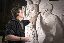 "BEFORE AND AFTER :  Richard Taylor, creative director of Weta Workshop, is pictured at work on the Rugby World Cup sculpture (left) and next to the finished product. ""I still spend about 80 percent of my workday down on the workshop floor, working with our team,"" explained Taylor. ""I got into this business to make cool stuff, and I never want to imagine that I foolishly put myself in a place where I'm so busy managing the cool stuff that I don't get to make it. I take great delight in being very hands-on."" - PHOTO BY STEVE UNWIN"