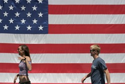 YOUNG AMERICANS :  A young couple passes a huge flag on their way to the parade. - PHOTO BY GLEN STARKEY
