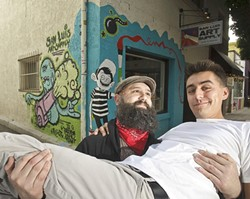 A TRICKY ANGLE? :  San Luis Art Supply owner Neal Breton (bearded, left) hired graffiti artists Nic Rodriguez (not pictured) and Julian Small Calvillo (cradled in Breton's arms) to paint a mural outside his shop. - PHOTO BY STEVE E. MILLER