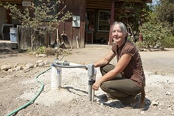 700 FEET DEEP:  Cindy Stevens crouches next to the top of her family's new well that was drilled in the past month at the cost of $27,000 to replace their 344 ft deep well that ran dry on June 20 of this year. The hose on the ground to the left provides water to her neighbor because their well recently ran dry also. - PHOTO BY STEVE E. MILLER