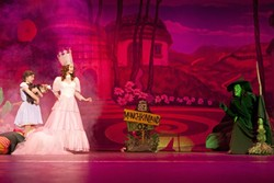 'WHERE TROUBLES MELT LIKE LEMON DROPS':  Dorothy (Cassie Johnson; left) finds herself in Munchkinland with Glinda the Good Witch (Allison King; pink gown), but is soon confronted by Glinda's nemesis, the Wicked Witch of the West (Theresa Riforgiate; green face), in Kelrik's 'The Wizard of Oz.' - PHOTO BY STEVE E. MILLER