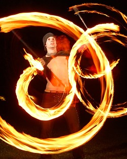 SPIN:  Chris Williams initially began spinning poi in Thailand, but he now practices his skill at the park. - PHOTO BY STEVE E. MILLER