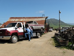 OFF THE FARM :  Tow company workers endeavor to haul away one of 26 vehicles county code officials had a warrant to remove from Dan DeVaul's Sunny Acres ranch. In the end, only six were removed. - PHOTO BY PATRICK HOWE