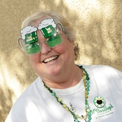 THE DRINKS ARE ON HER :  DeAnn Troutner was peddling green beer, Jameson, and corned beef and cabbage burritos. - PHOTO BY STEVE E. MILLER