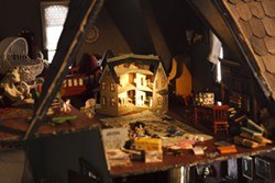 TINY VOYEURS :  Peeking into the attic of Kroll's dollhouse feels almost like spying, it's so detailed. In a rather witty touch, the artist has even included a miniature replica of the dollhouse itself. Wow.