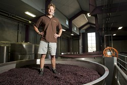 WALKING ON WINE :  Fin du Fresne, winemaker at Chamisal Vineyards, showed off his ability to walk on a Pinot Noir cap in his winemaking facility. - PHOTO BY STEVE E. MILLER