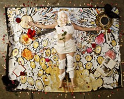 SMILE! :  Painter Josephine Crawford lies inside the outline of herself in her mixed media art piece The Big Bang. Artist Lena Rushing created the disturbingly accurate portrait on her face. - PHOTO BY STEVE E. MILLER