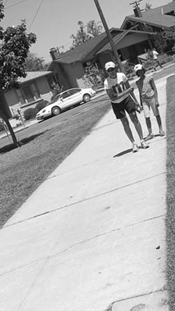 TOUR DE MITCHELL PARK HOPSCOTCH MARATHON :  Mignon Khargie and her daughter are the sole hopscotchers during New Art Collective's failed hopscotch tournament on Aug. 2. - PHOTO BY ASHLEY SCHWELLENBACH