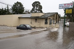 DROWNING :  Drainage problems caused massive flooding and damage at Pacific Coast RV in Pismo Beach. From left to right: Mechanic Daren Lenton drives his car off the flooded lot; owner Shaun Brewer wades through water he said was twice as high the night before; and employee Craig Mase uses a forklift to drag an RV off the lot. - PHOTO BY STEVE E. MILLER
