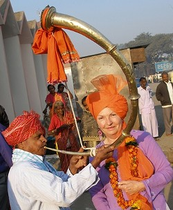 """THE ILLUSTRIOUS AUTHOR :  The Joy of Sexus author Vicki Leon traveled extensively and took up odd jobs in several countries throughout the Mediterranean before she began writing about the ancient world. Here, she's pictured on a trip to India. """"I immediately noticed that the horn players were using a 'cornu,' the ancient Roman horn that was played in the gladiatorial arena as well as in military settings,"""" Leon writes of this photograph. """"So there I am, squinting in the early morning sun and thrilled with finding yet another clue to the antiquity I so love."""" - PHOTO COURTESY OF VICKI LEON"""