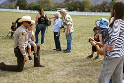 GOOD GUY WITH A GUN:  SLO County Sheriff Ian Parkinson takes a knee for a photo op with a young admirer. - PHOTO BY GLEN STARKEY