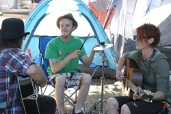 PRACTICE MAKES PERFECT :  (left to right) Sam Boorman, Molly Reeves, and Kenneth Davis—three members of the six-piece Red Skunk Jipzee Swing Band—practice in their campsite a few days before their main stage appearance. - PHOTO BY GLEN STARKEY