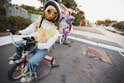 RIDE ALONG:  One of the most popular scarecrow installations in town features a working bicycle with two straw-stuffed riders atop. - PHOTO BY KAORI FUNAHASHI