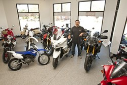 SHINY TWO WHEELED MACHINES:  Surrounded by just some of SLO Motorsports stock of Yamahas, Moto Guzzis, Aprilias, Vespas and Piaggio, manager Lance Tanneris is ready to help you buy your next motorcycle. - PHOTO BY STEVE E. MILLER
