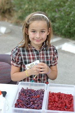 MACARONI NECKLACE QUEEN :  Sevryn Jiminez, 9, crafts a necklace at one of the craft stations set up during the Salon 544 silent auction. - PHOTO BY GLEN STARKEY