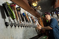 LIBERATE THE FLAVOR :  Bar manager Tyler Clark keeps 20 taps connected to a rotating supply of the world's best beers at the newly opened Libertine Pub, 801 Embarcadero Road. - PHOTO BY STEVE E. MILLER