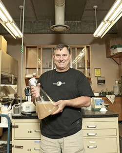 """THE PITCH :  Using 45-million-year-old yeast harvested from fossilized amber, Dr. Raul Cano, a Cal Poly microbiologist, brews beer. He's used the same samples collected in 1996 to create the """"pitch"""" used as a base in the brewing process. - PHOTO BY STEVE E. MILLER"""