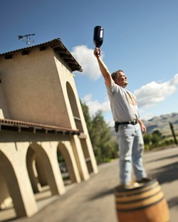 ONE FOR ALL :  Vintner Mike Sinor stands triumphant at the old Corbett Canyon Winery. - PHOTO BY STEVE E. MILLER