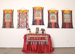 DEITIES BY THE HANDFUL :  Five thankas from the exhibit, depicting five different Buddhas or deities, are mounted on silk brocade backgrounds. The center column beneath the image represents a door through which people can enter the thanka. - PHOTO BY STEVE E. MILLER