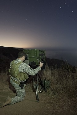 EYES ON THE WATER :  A National Guard soldier peers through a LRAS-3 long-range night vision scope to scan the horizon for suspicious watercraft. The U.S. National Guard's counter-drug coastal surveillance team took New Times for a ride-along atop the hills overlooking the Ventura County coastline. - PHOTOS BY STEVE E. MILLER