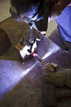 Alan Baxter welds the base of the bronze to the microphone figurine. - PHOTO BY STEVE E. MILLER
