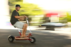 ELECTRIC PERSONALITY :  San Luis Rides owner, Jake Carter, buzzes past traffic on an electric Go-Ped Scooter. - PHOTO BY STEVE E MILLER