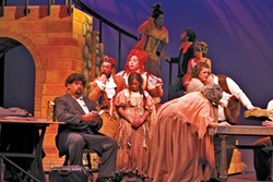 MASTER OF THE HOUSE:  Nik Johnson (center, hand in mouth) and Robin Kirk Wolf (red hair) play the crooked Madame and Monsieur Thénardier in Chameleon Productions' Les Miserables. - PHOTO BY AUDREY HOWARD