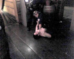 BLURRY BUT SUFFICIENT:  This photo, reportedly showing Officer Nicole Canby pinning Brian Lopez Martinez to the ground, was taken by cell phone and posted to Craigslist after the incident. - FILE IMAGE VIA CRAIGSLIST AND BRIAN LOPEZ MARTINEZ