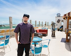 THE ROOF IS ON FIRE :  Gaviota Grill Head Chef Jesse Morrow shows off the new restaurant's crown jewel: a rooftop patio seating area complete with heaters, funky maritime décor, and an unobstructed seaside sunset view. - PHOTO BY KAORI FUNAHASHI