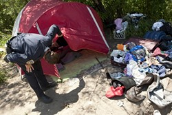 ANYBODY HOME? :  SLO Police Officer Kevin Waddell checks in on two illegal campers near San Luis Obispo Creek while on a CAT (Community Action Team) shift.