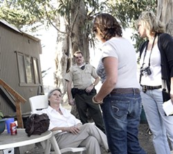 TOLD TO LEAVE :  Darcene Clayton, sitting, gets the news from county code enforcers Marie Cowan and Jill Bennet, as deputy Jay Wells (stands by), that she'll have to leave the mobile home she lives in on the Sunny Acres ranch. - PHOTO BY STEVE E. MILLER