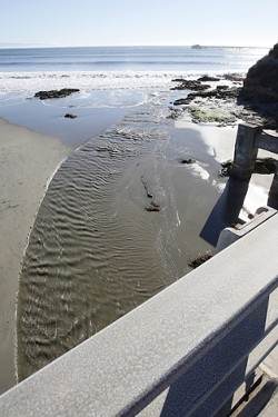 WHERE DOES IT GO? :  Creeks that empty into the ocean, like this one flowing into Avila Bay, carry along debris and fluids washed from storm drains and gutters. County supervisors recently tentatively approved a new ordinance written to protect local waters from chemicals and trash. - PHOTO BY STEVE E. MILLER