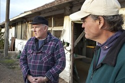 RAIDED :  Henri DeGroot (left), owner of the 40-acre former chicken farm that was searched last month, and John Brigham (right), who operates a recycled furniture woodshop on the property, claim that there was something fishy about a recent raid. - PHOTO BY STEVE E MILLER