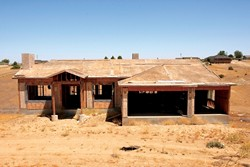 INTERESTED IN HALF A HOUSE? :  Work has stopped on this half-finished Paso Robles house. It's one of dozens financed through 21st Century and other hard-money lenders that are now in the foreclosure process. - PHOTO BY STEVE E. MILLER
