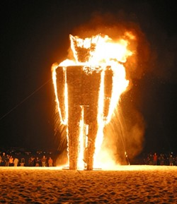 FIRE MAN:  This summer, a hundred-something people congregated in the Oceano Dunes and built a massive wood-and-wire-framed man and stuffed it with hundreds of thousands of pieces of junk mail. Then they lit it on fire.