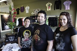 SACRED THREADS: :  (From left to right) Art director Jaime Alatore, owner Jon Broyes and Lauren Carlsted, who does marketing and public relations, show off their original T-shirt designs at the Something Sacred store in San Luis Obispo on Los Osos Valley Road.
