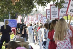 LINE OF SIGNS :  On July 26, members of the California Nurses Association and other supporters marched with signs and shouted slogans to call awareness to ongoing negotiations with Catholic Healthcare West. - PHOTO BY STEVE E. MILLER