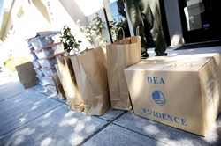 TAKE IT AWAY :   Unpacking shot - Detectives seized more than marijuana from Central Coast Compassionate Caregivers. They also carted away several hard drives, bags of items, and cardboard boxes. - PHOTO BY JESSE ACOSTA