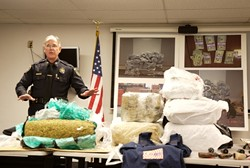 A LOT OF DOPE :  On Jan. 24, SLOPD Capt. Dan Blanke stood behind a table displaying a fraction of the almost 750 pounds of marijuana seized during a yearlong investigation into an international smuggling ring that ran through San Luis Obispo. - PHOTO BY JESSE ACOSTA