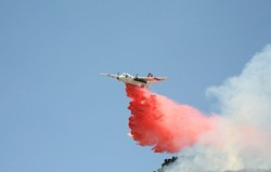 BOMBS AWAY :  A CDF bomber dropped a payload of fire retardant - compound on a field of wildfire fuel on June 23. - PHOTO BY JESSE ACOSTA
