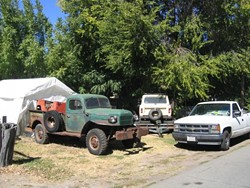 VALUABLE VEHICLES? :  Ken Slusser collects and restores military vehicles, which he keeps in his Santa Margarita yard. SLO County code enforcement officials are issuing clean-up orders and fines for vehicles stored outdoors in the Santa Margarita area, and are telling Slusser to pay up. - PHOTO BY KATHY JOHNSTON