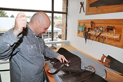 HANDMADE:  Ty Smith hand cuts and sews every leather item, like wallets and messenger bags, sold at Hide and Tallow in Cambria. - PHOTO BY DYLAN HONEA-BAUMANN