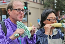FOOD TOURISTS:  Carolyn Nakano and Brett O'Sullivan, visitors from Boulder, Colo., don't care if they've got corn on their face and butter dripping down their chin. - PHOTO BY DYLAN HONEA-BAUMANN