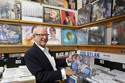 TAKES ME BACK:  Glen Blosser flips through old David Bowie records at Boo Boo Records in San Luis Obispo, where his photos of the legendary glam rocker are currently up on display. - PHOTO BY DYLAN HONEA-BAUMANN
