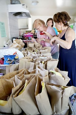 PEOPLE'S KITCHEN:  Volunteers Debbie, Clara, and Mary (left to right) prepare paper bag dinners at Second Baptist Church in Paso Robles for locals in need. The People's Kitchen is able to serve dinners Monday through Friday because of the efforts of faith-based organizations. - PHOTO BY DYLAN HONEA-BAUMANN