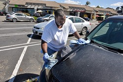"SPRAY ON, WIPE OFF:  Lamar Harrison from Clean and Green Auto Care ""washes"" a car in the Smart & Final parking lot off Grande Avenue in Arroyo Grande without using any water. - PHOTO BY CAMILLIA LANHAM"